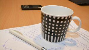 Kynä, kahvimuki ja muistiinpanoja paperilla