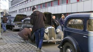 ihmiset tutkivat vanhoja autoja Ylen pihalla