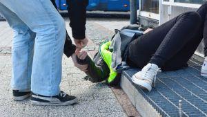 Mies mittaa maassa makaavan naisen pulssia.