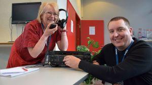 Kaksi radioamatööriä ottaa yhteyksiä radiolaitteella ja poseeraa kameralle