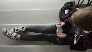 Nuori nainen katsoo kännykkäänsä.