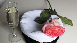 Ylioppilaslakki, ruusu ja lasi kuohuviiniä.
