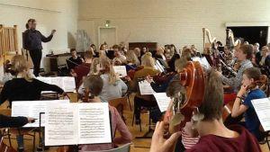 Kuvassa kapellimestari Atso Almila johtaa musiikkileirin orkesteria.