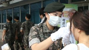 Korealaissotilaat tarkastavat Korean puolustusministeriöön tulevia ihmisiä MERS-viruksen vuoksi.