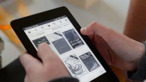 Henkilö käyttää Kindleä, jolla voi lukea sähköisiä kirjoja.