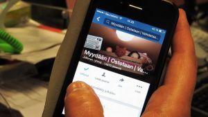 Facebook-kirpputoriryhmää selataan kännykän näytöltä.