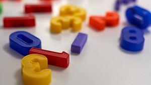 Keltaisia, punaisia ja sinisiä muovinumeroita vaalealla pöydällä.