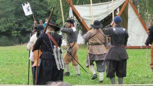 Kuvassa marssi jalkaväen sotilaita, jotka ovat pukeutuneet 1600- luvun asuihin. Taustalla näkyy valkea teltta ja järven pintaa.