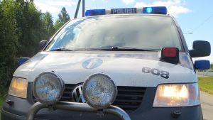 Poliisiauto parkissa vilkut päällä.