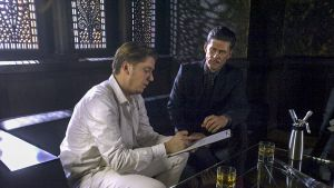 kasi miestä istuu sovalla, toinen kirjoittaa lehtiöön