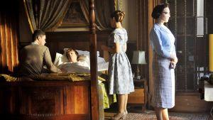 nainen vuoteessa, vuoteella istuu mies, kaksi naista seisoo huoneessa