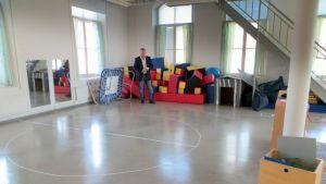 Aikuinen mies seisoo tyhjällä lattialla