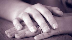 Käsi pitelee toista kättä.