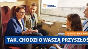 Perhe matkustaa junassa ja pääministeri Ewa Kopacz juttelee heidän kanssaan.
