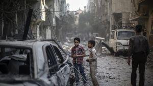 Kaksi poikaa seisoskelee kadulla ilmaiskun jälkeen Doumassa, Damaskoksen esikaupungissa.