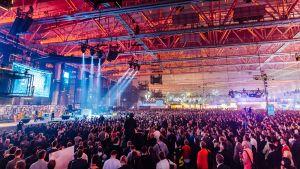Kuvassa ihmisä suuressa hallissa, vasemmalla esiintymislava, valonheittäjiä.