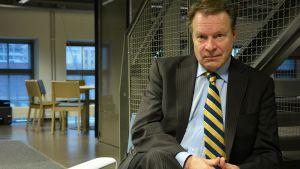 Ilkka Kanerva istuu tuolilla ja katsoo kameraan.
