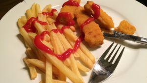 Ranskanperunoita, kalapuikkoja ja ketsuppia lautasella.