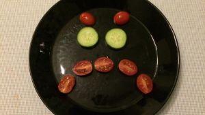 Kurkkuviipaleista ja tomaateista tehty vihainen naama lautasella.