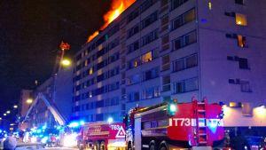 Kahdeksankerroksisen kerrostalon katolta näkyy tulenlieskoja.