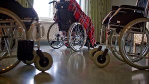 Vanhus istuu pyörätuolissa.