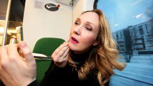 Janita Salmensuo meikkaa junassa.