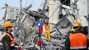 Sotilaspukuisia miehiä pahoin tuhoutuneen talon raunioilla.