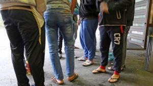 Turvapaikanhakijat ovat pukeutuneet varvastossuihin.
