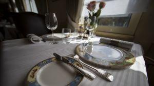 Hämyinen tunnelmakuva ravintolapöydästä astioineen ja ruusuineen.
