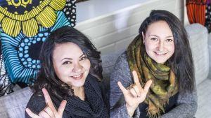Viittomakieleksi musiikkikappaleita muuttavat Nina Kukkaslahti ja Alisa Nissinen näyttävät rakkauden merkkiä