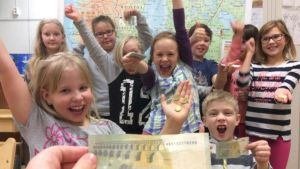 Valkeakosken Rauhalan 4H-kerhon lapsilla seteleitä ja kolikoita kädessä.
