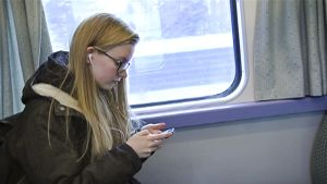 Abi käyttää junassa matkustaessaan älypuhelintaan.