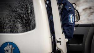 Poliisi poliisiauton sivuovella.