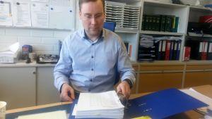 Rikoskomisario Petri Savela Oulun poliisilaitoksella työhuoneessaan pöydän ääressä taustalla kirjahyllyssä mappeja.
