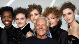 Muotisuunnittelija Giorgio Armani valokuvamallien ympäröimänä.