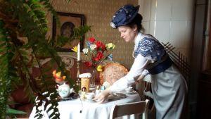 Historialliseen asuun pukeutunut nainen laittaa kahvipöytää