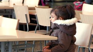 Lapsi istuu yksin pöydässä.