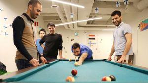 Mustafa Shakir pelaamassa biljardia muiden kanssa.