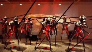 Keskiaikaisia haarniskoituja jalkamiehiä taistelumuodostelmassa näyttelyssä