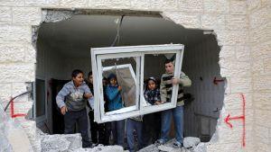 Kuusi pikkupoikaa pitelee paikaltaan irrotettua ikkunaa talon raunioissa.
