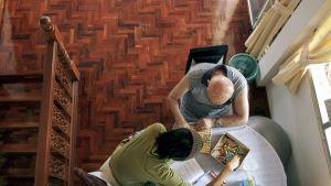 Dementiasta kärsivä vanhus pelaa peliä hoitajan kanssa. Kuva ylhäältä.