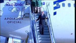 Silmälasipäinen mies tummassa puvussa laskeutuu lentokoneesta portaita alas lyhdynnäköinen kullankeltainen esine kädessään. Koneen kyljessä on olympiarenkaat ja siinä lukee Rio 2016, Apoiador oficial.