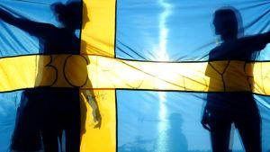 Fanit kannattelevat Ruotsin lippua urheilutapahtumassa.