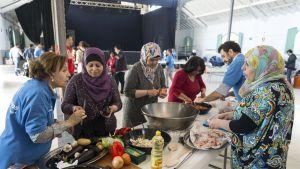 Viisi naista ja yksi mies seisoo pöydän ääressä valmistamassa ruokaa.