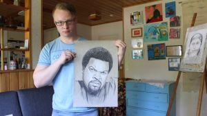 Akke Saari esittelee piirtämäänsä kuvaa muusikko Ice Cubesta.