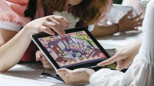Tytöt pelaavat tabletilla.