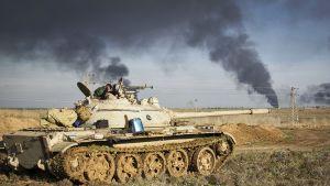 Tankki kuvan etualalla, taustalla horisontissa nousee kaksi syvänsinistä savuvanaa.