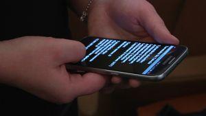 Siivousyritys Puhdas Ilon työntekijän käsissä oleva kännykkä, jossa tietoja siivouskohteesta.