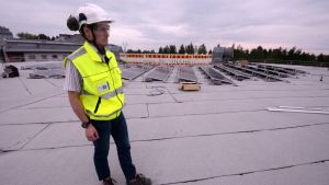 KYS kiinteistöjohtaja Mikko Hollmén esittelee pysäköintitalon katolla aurinkopaneeleita.