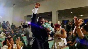 McLaurenin perhe Norfolkista on juuri kuullut saaneensa rahalahjan, joka riittää luottovelkojen maksamiseen. Musta mies on nostanut oikean kätensä ylös. Hänen vasen kätensä pitelee pientä lasta.